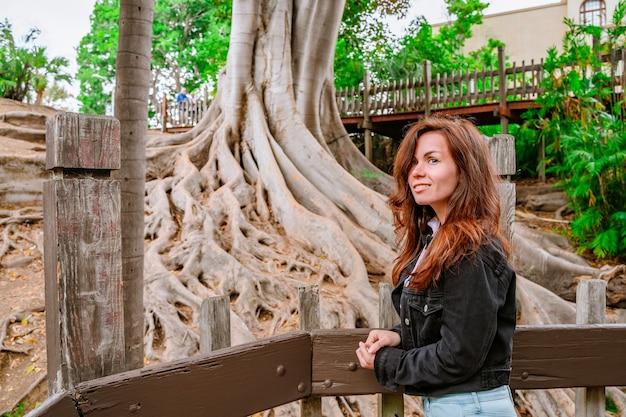 美しい女性は、バルボアパークサンディエゴの巨大な根を持つ木々と熱帯雨林を歩きます