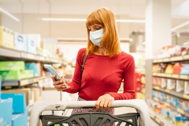Красивая женщина waring защитная маска, держа смартфон рецепт чтения. покупки в пандемическом карантинном магазине в супермаркете. коронавирусная концепция