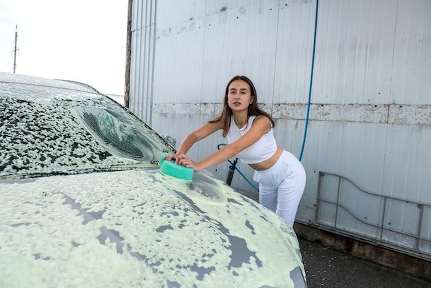 아름 다운 여자는 더러운 거품에 녹색 스폰지로 그녀의 차를 씻는다