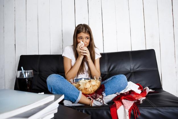 Bella donna guardando melodramma, piangendo, seduto sul divano di casa.