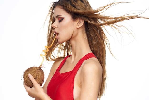 夏のライフスタイルの明るい背景を楽しむ手で美しい女性のウェーブのかかった髪のココナッツカクテル