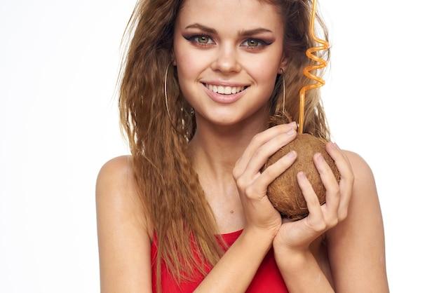 夏のライフスタイルの光を楽しんでいる手で美しい女性のウェーブのかかった髪のココナッツカクテル。
