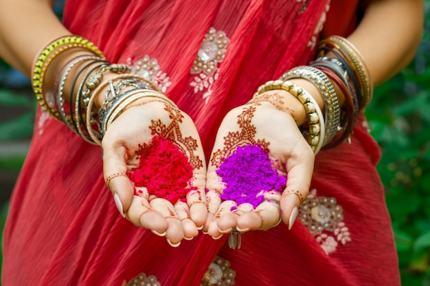 Beautiful woman wear traditional indian wedding red sari dress hold in hands with henna tattoo and bracelets colorful pink violet holi dust powder paint. happy holiday summer culture festival concept