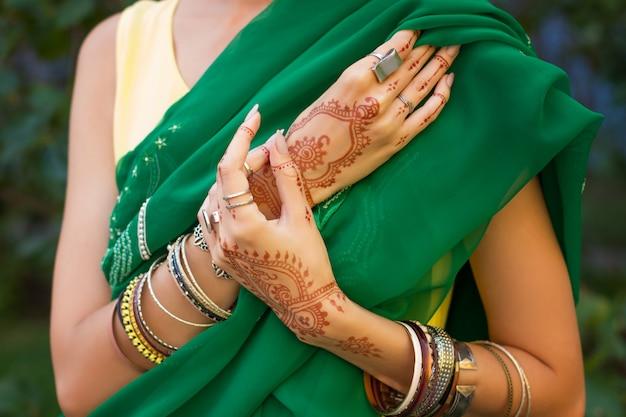 아름 다운 여자 헤나 문신 멘디 패턴 보석 및 팔찌와 전통적인 이슬람 아랍어 인도 결혼식 녹색 사리 드레스 손을 착용하십시오. 해피 홀리데이 여름 문화 축제 축하 개념.