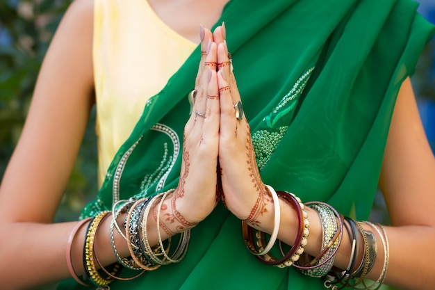 Beautiful woman wear traditional muslim arabic indian wedding green sari dress hands with henna tattoo mehndi pattern jewelry and bracelets. folded her hands in meditation prayer. religion concept.