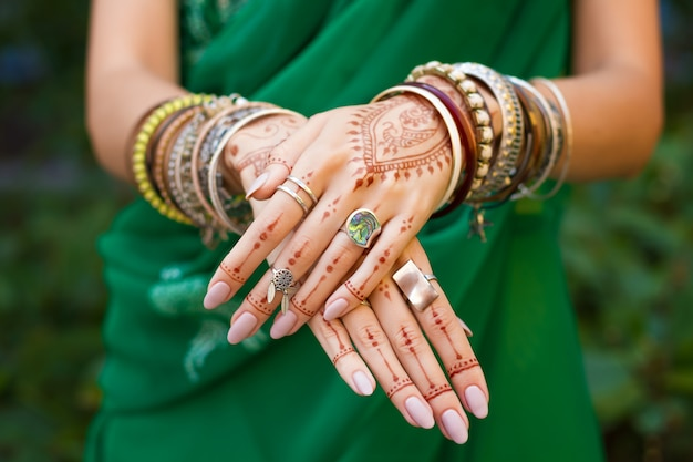 Beautiful woman wear traditional muslim arabic indian wedding green sari dress hands with henna tattoo mehndi pattern jewelry and bracelets. happy holiday summer culture festival celebration concept.