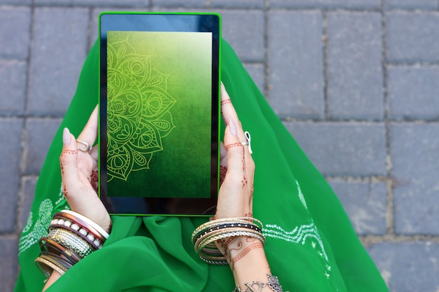 Beautiful woman wear traditional muslim arabic indian wedding green sari dress hands with henna tattoo mehndi pattern jewelry and bracelets hold tablet. summer culture festival celebration concept.
