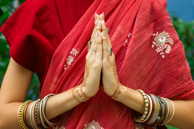Beautiful woman wear traditional muslim arabic indian wedding pink red sari dress hands with henna tattoo mehndi pattern jewelry and bracelets. folded her hands in meditation prayer. religion concept.