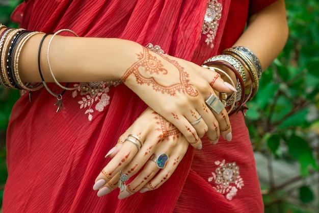 아름 다운 여자 헤나 문신 멘디 패턴 보석과 팔찌 해피 홀리데이 여름 문화 축제 축하 개념 전통적인 이슬람 아랍어 인도 결혼식 레드 핑크 사리 드레스 손을 착용