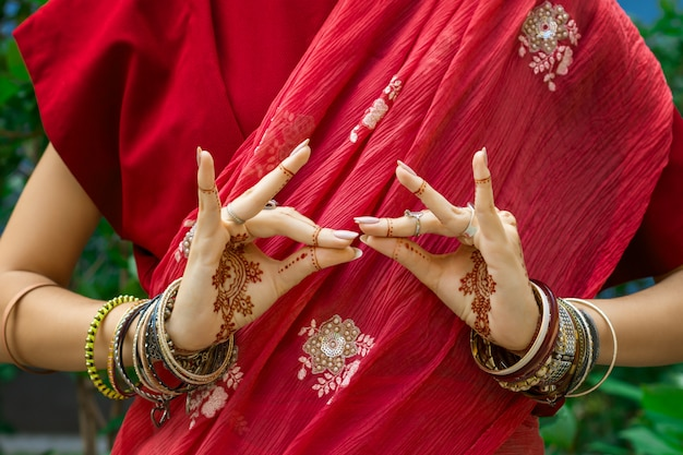Beautiful woman wear traditional muslim arabic indian wedding red pink sari dress hands with henna tattoo mehndi pattern jewelry bracelets do hands dance movement. holiday culture festival celebration