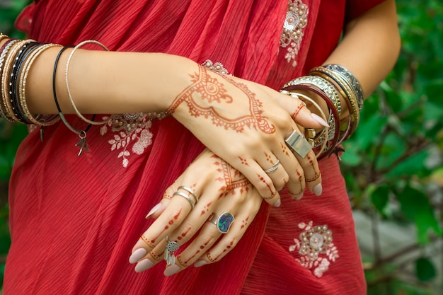 Beautiful woman wear traditional muslim arabic indian wedding red pink sari dress hands with henna tattoo mehndi pattern jewelry and bracelets happy holiday summer culture festival celebration concept