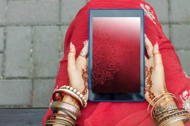 Beautiful woman wear traditional muslim arabic indian wedding red pink sari dress hands with henna tattoo mehndi pattern jewelry and bracelets hold tablet. summer culture festival celebration concept.