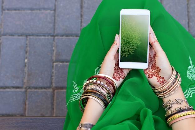 아름 다운 여자 헤나 문신 멘디 패턴 쥬얼리와 팔찌 전통적인 이슬람 인도 결혼식 녹색 사리 드레스 손을 착용하고 흰색 스마트 폰을 개최합니다. 여름 문화 축제 축하 개념