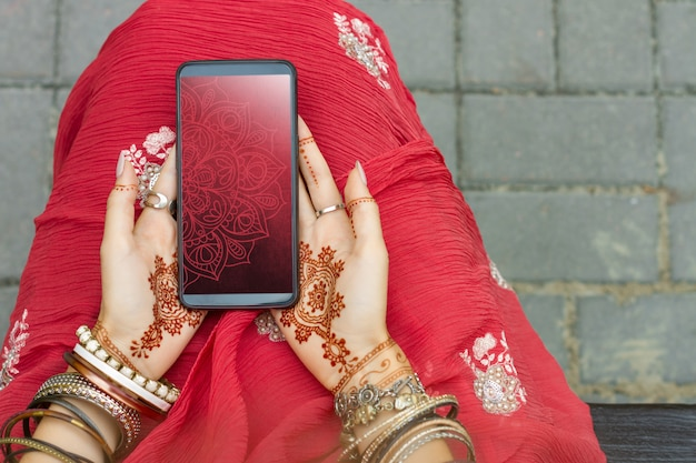 Beautiful woman wear traditional muslim indian wedding red pink sari dress hands with henna tattoo mehndi pattern jewelry and bracelets hold smartphone. summer culture festival celebration concept