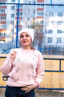 뒷면에 아이스 스케이트와 분홍색 스웨터와 모자에 weared 아름 다운 여자 겨울 눈 덮인 공원에서 산책.