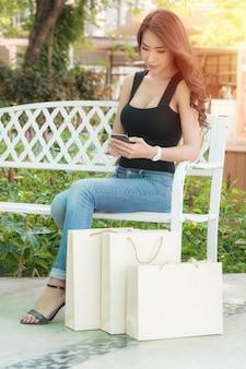 Красивая женщина в черной рубашке и джинсах с идеальной формой тела сидит в кресле с сумкой для покупок в открытом торговом центре вечером, когда светит красный свет.