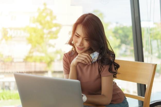 갈색 셔츠를 입고 큰 창가에 앉아 행복한 얼굴로 웃고 있는 아름다운 여성, 그녀는 노트북으로 온라인 쇼핑을 하고 신용 카드를 들고 있습니다.