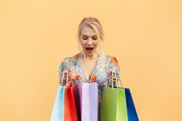 Красивая женщина в платье с хозяйственными сумками на оранжевом пастельном фоне. понятие торговых покупок и продаж
