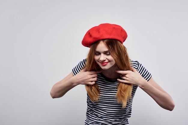 明るい背景のポーズをとって赤い帽子メイクフランスヨーロッパファッションを身に着けている美しい女性