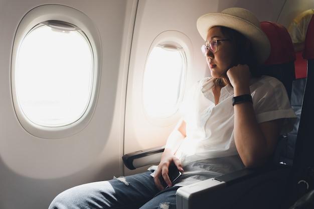 飛行機に坐っている間スマートフォンを使用して麦わら帽子をかぶっている美しい女性