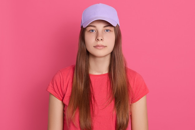 Красивая женщина носить бейсболку и футболку позирует, изолированные на розовой стене с серьезным выражением на лице, с длинными прямыми волосами.