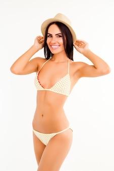 Красивая женщина в бикини и шляпе, наслаждаясь летом