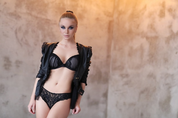 Beautiful woman wearing black leather jacket and sexy black lingerie