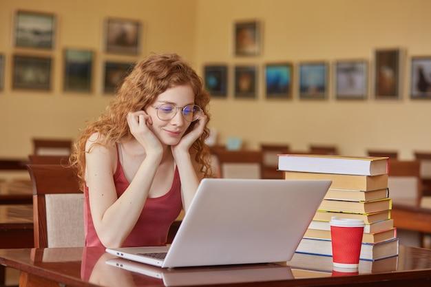 Красивая женщина в бордовой повседневной футболке и очках читает текст через ноутбук или ищет необходимую информацию