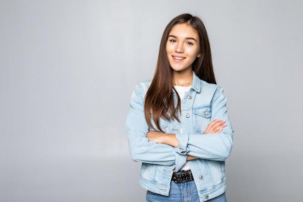 Красивая женщина нося вскользь джинсовую куртку над изолированными руками стены совместно и пальцы пересекли усмехаться расслабленный и жизнерадостный. успех и оптимизм