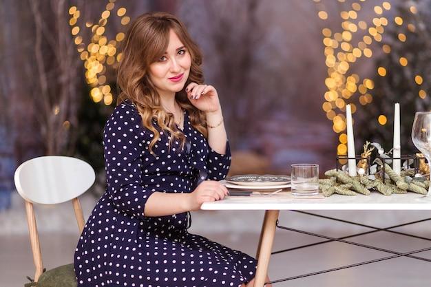Красивая женщина в платье за рождественским столом