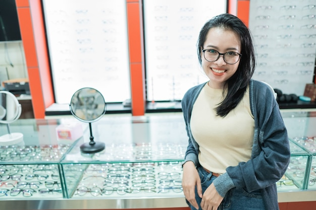 A beautiful woman wearing glasses of her choice and posing in front of an eyeglass window at an eye clinic