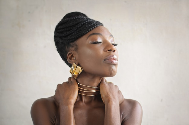 Beautiful woman wearing golden earrings and necklace
