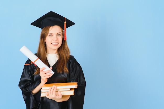 Красивая женщина в выпускной кепке и церемониальной мантии, имеющей степень, выглядит позитивной и счастливой, стоя и улыбается с уверенной улыбкой.