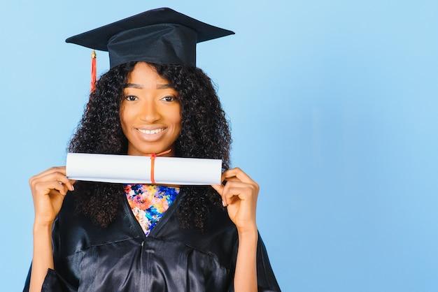 졸업 모자와 예복을 입은 아름다운 여성이 학위를 들고 긍정적이고 행복해 보이고 자신감 있는 미소로 웃고 있습니다.