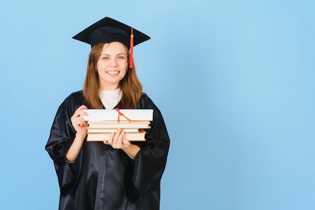 卒業式の帽子と儀式用のローブを身に着けている美しい女性は、前向きで幸せそうに見え、自信を持って笑顔で笑っています。