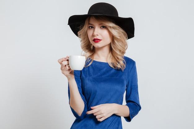 一杯のコーヒーを保持している帽子をかぶっている美しい女性