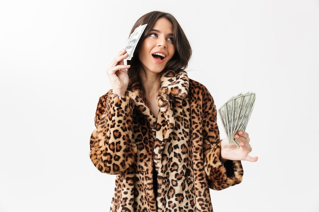Beautiful woman wearing leopard fur coat standing isolated over white, showing money banknotes