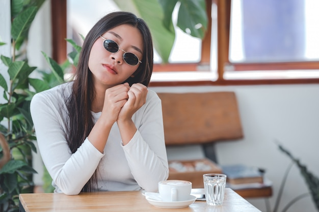 A beautiful woman wearing a long-sleeved white shirt sitting at a coffee shop