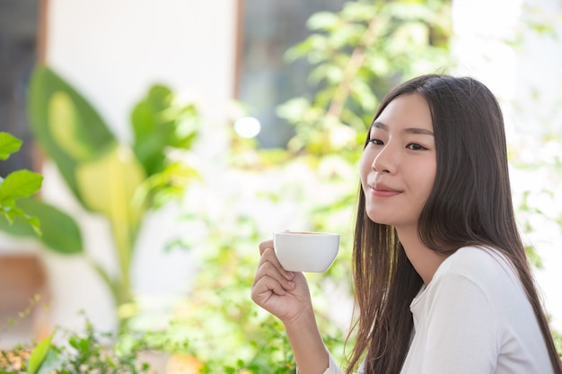 Beautiful woman wearing a long-sleeved white shirt sitting at a coffee shop