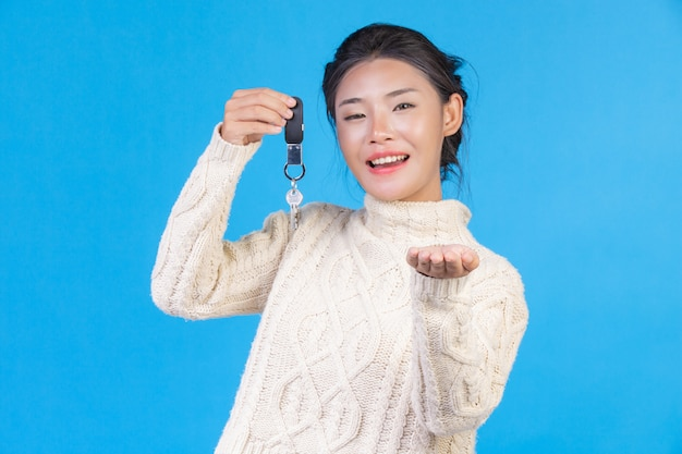 Beautiful woman wearing a new long sleeved white carpet, holding a key ring in the hand on a blue . trading  s.