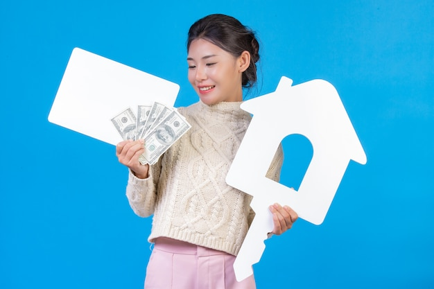 Beautiful woman wearing a new long sleeved white carpet that holds the house symbol. white plaque and dollar bill on a blue . trading .
