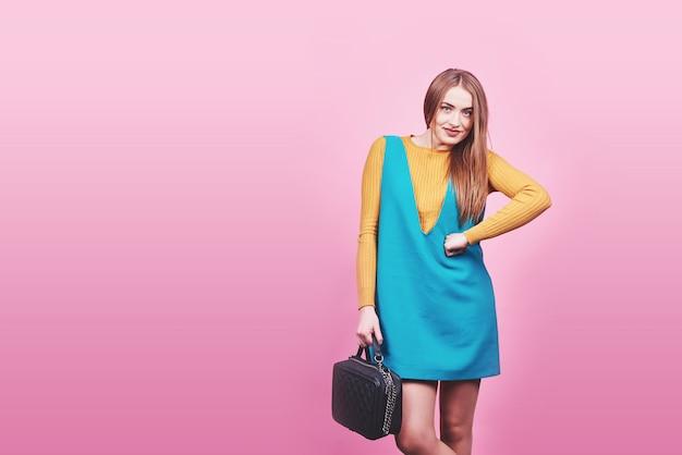 좋은 옷을 입고 아름 다운 여자 핸드백 핑크에 포즈.