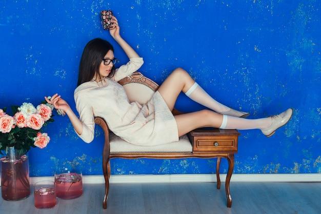 청록색 배경에 포즈 좋은 옷을 입고 아름 다운 여자. 패션 봄 사진