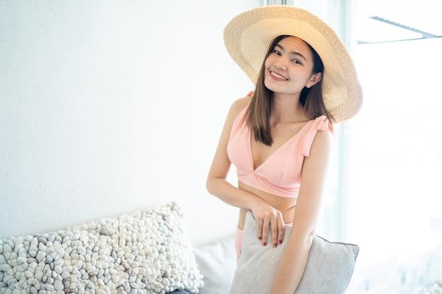 Beautiful woman wearing pink bikini sit on a comfortable seat in the room.