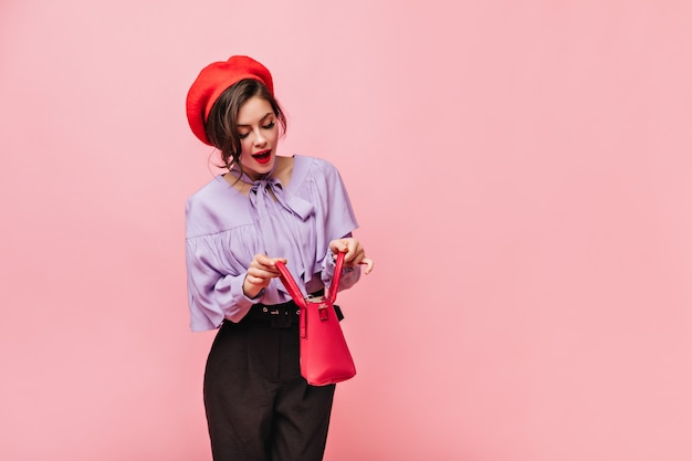 Beautiful woman wearing red beret, blouse and black pants peeks into open bag.