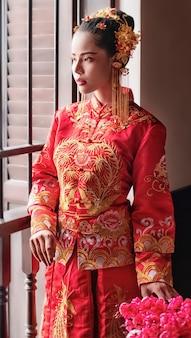 The beautiful woman wearing red dress standing beside window