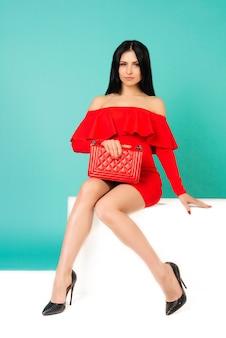 흰색 벤치에 앉아 하이힐 구두와 지갑 손 가방 빨간 드레스를 입고 아름다운 여자-이미지