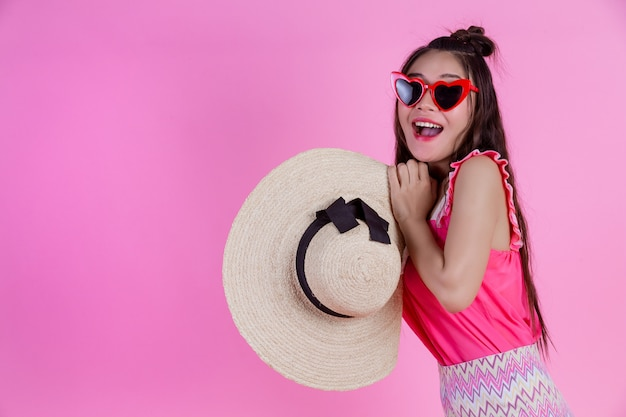 A beautiful woman wearing red glasses with a big hat on a pink .