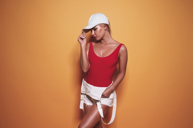 Beautiful woman wearing a red swimsuit and baseball cap posing on yellow
