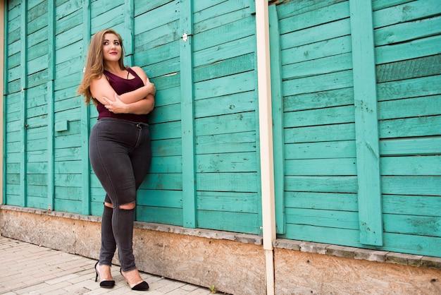 街でカフェの壁に立っている破れたジーンズを身に着けている美しい女性。カジュアルファッション、毎日の優雅な表情。プラスサイズモデル。